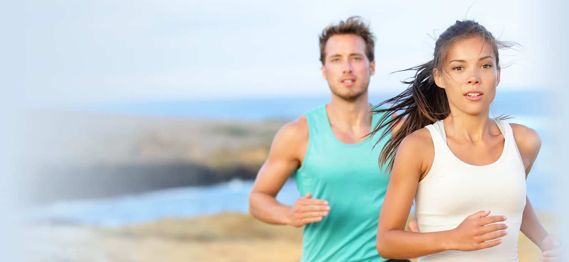 Couple running on beach after recovering faster from sports injuries with PRP injection therapy
